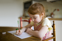 little girl sitting at table writing in notebook