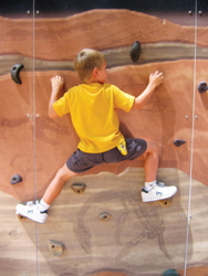 Dinosaur Revolution Maze; child climbing rock wall; rock climbing; boy