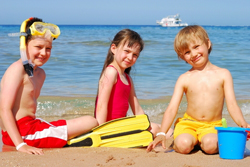 kids on beach; children playing on a beach, in the sand, in the water