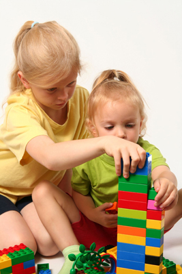 special needs child with sibling; young girls playing with blocks, legos