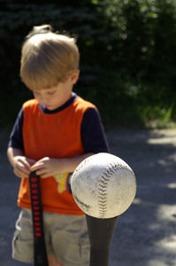 young boy playing t-ball; tee ball; little boy upset from losing baseball game