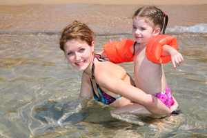 mom and daughter swimming at the beach; mom and daughter in the ocean; mom teaching daughter how to swim
