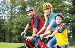 family biking together; parents and son riding bikes; bicycling; family wearing bike helmets