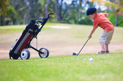 young boy playing golf; little boy hitting golf ball