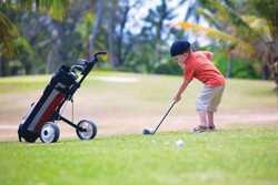 young boy playing golf; little boy hitting golf ball; golf lessons in Manhattan