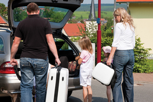 family packing the car; family vacation; parents and child preparing to travel; travelling with a special needs child