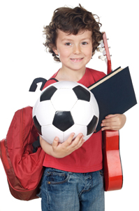 child juggling several activities; child holding soccer ball, guitar, and school books, backpack, bookbag