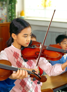 young girl playing a violin; child in music class; after-school activities