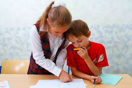little girl and boy doing schoolwork; brother and sister doing their homework; sister helping brother with homework