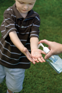 little boy using hand sanitizer; child using Purell