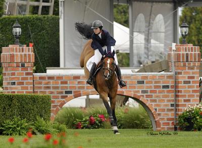 Hampton Classic Horse Show; huntseat rider jumping a brick wall; equestrian