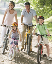 family riding bikes; family on bicycles with helmets