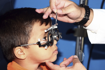 child getting vision checked; little boy at eye doctor's office, vision screening
