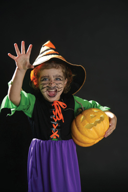 Little girl in scary halloween costume holding pumpkin; young girl dressed up as a witch for Halloween