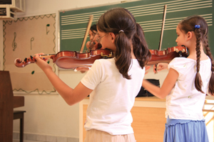 children, girls playing violin; music class in school