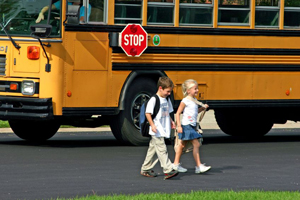 young boy and girl crossing in front of a school bus; school bus safety