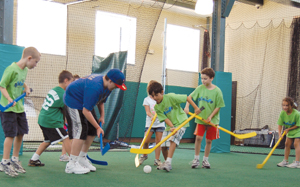 Vision Sports Club; kids playing floor hockey