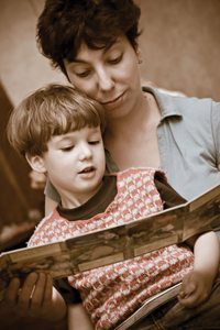 mom reading a book with young son