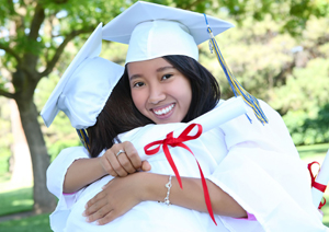 high school graduates hugging while holding diploma; asian woman graduating