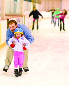 dad helping young daughter ice skate; ice skating rink