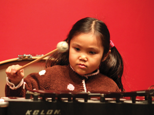 young girl playing the xylophone