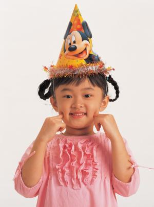 asian girl in a party hat; young girl at a birthday party