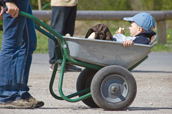 child in wheelbarrow; volunteers outside