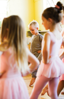 young boy in dance class surrounded by girl ballerinas