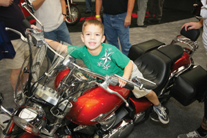 child at motorcycle show; little boy sitting on motorcycle