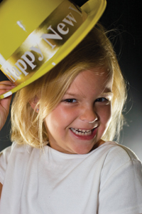 little girl wearing a happy new year hat