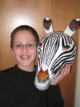 boy holding zebra mask