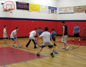 kids playing floor hockey; gym class; indoor gym