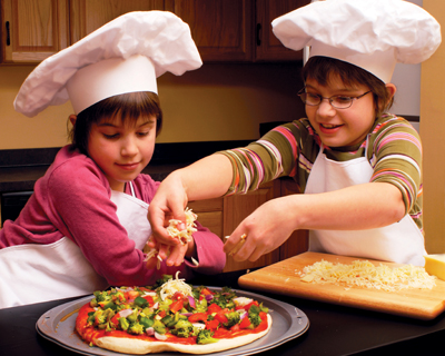 brother and sister making pizza, wearing chef hats