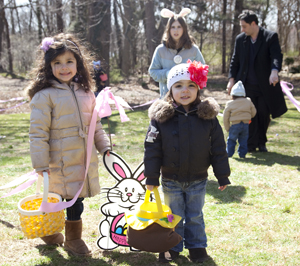 Easter egg hunt; two young girls holding Easter baskets