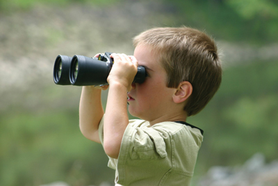 child with binoculars; boy bird watching