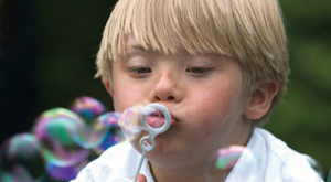 boy with down syndrome blowing bubbles