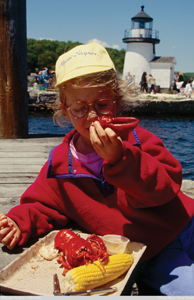 little girl eating lobster by the bay