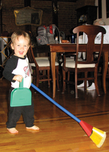 little boy having fun sweeping the floor