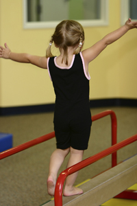 young girl on beam in gymnastics class