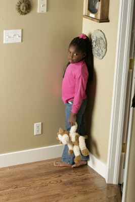 little girl standing in the corner of the room holding stuffed animal
