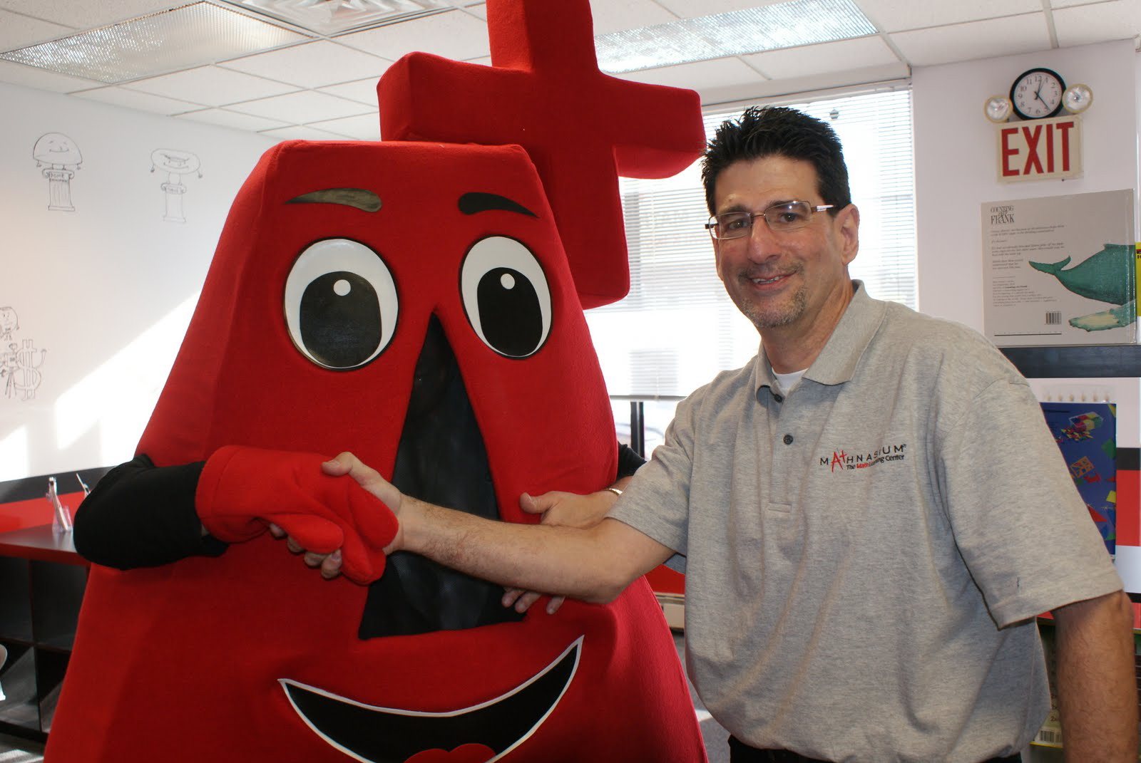 Mathnasium of New Hyde Park center director Peter Abrams greets mascot A+ at  the grand opening on January 16.