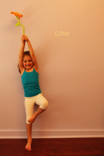 little girl doing yoga tree pose