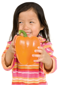 little girl holding orange pepper
