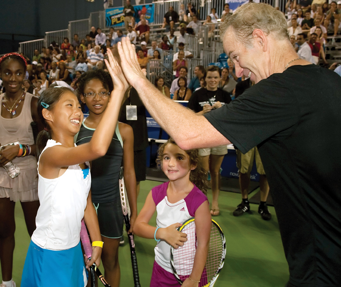 John McEnroe high-fives student at his tennis academy try outs.