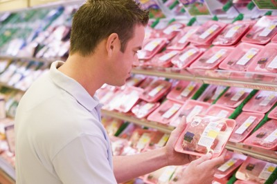 reading meat labels in supermarket