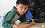 Boy Experimenting with Toy Car