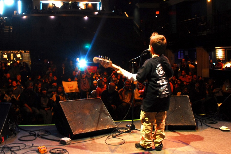 child playing guitar on stage