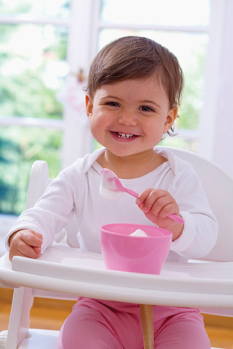 toddler in high chair eating yogurt