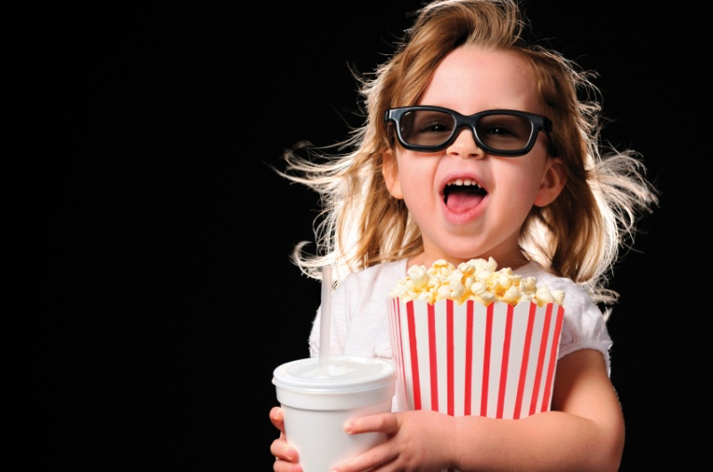 little girl at movies with 3d glasses and popcorn