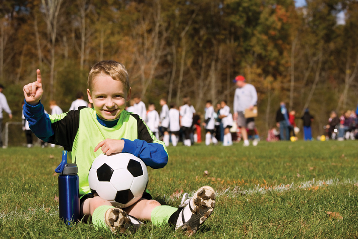 young boy with soccer ball on field